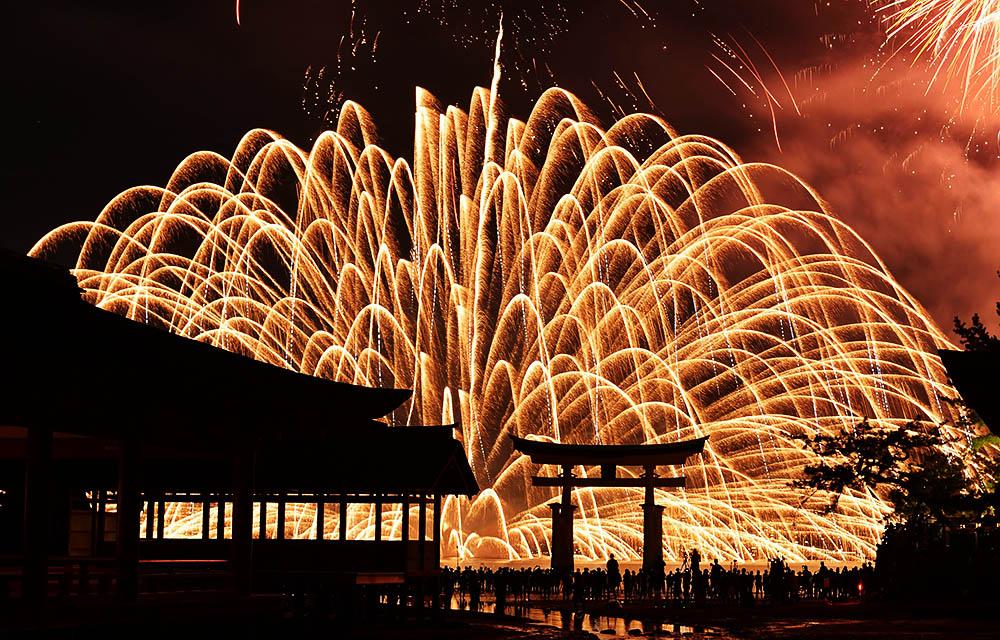 当地时间2016年8月11日,日本廿日市,宫岛水上烟花大会举行,世界遗产严岛神社的鸟居在烟花映照下现出剪影。